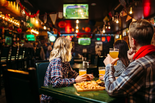 A group of people are sitting at a table in a sports bar. Their backs are towards the camera as they are watching a sports game on TV and drinking beer.