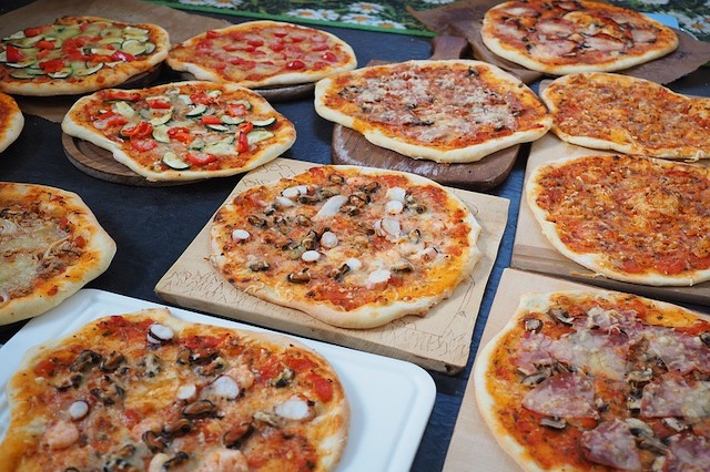 Lots of different pizzas laid out on a table