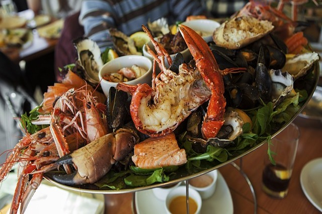 a red basket filled with two fried fish tacos, french fries, fried corn on the cob, and a small cup with mango salsa with a beer bottle in the background.