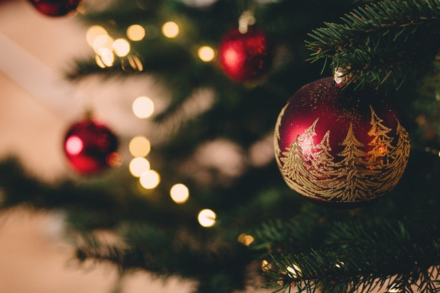 A close up of a red ornament with gold trees on a Christmas tree.