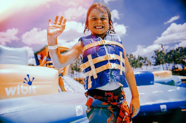 A child wearing a life vest and swim suit is smiling and waving in front of the inflatable water park at Shark Wake Park