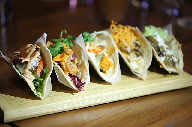 A variety of authentic soft tacos in a row on a wooden plate