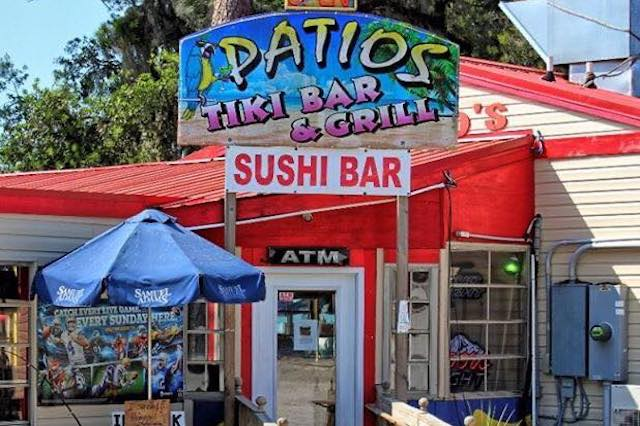 The exterior of Patio's Tiki Bar and Grill in Little River, SC. It's a tan building with a red roof. There is a large colorful sign with the restaurant's name and a painting of a parrot with palm trees on the top of the building.